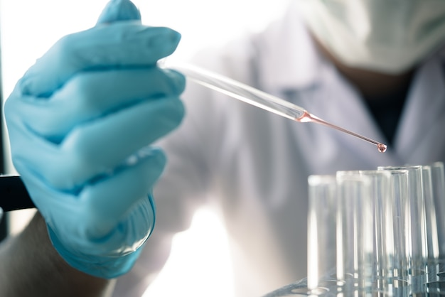 Ученые капают жидкость в пробирку. поиск в лабораторных концепциях.