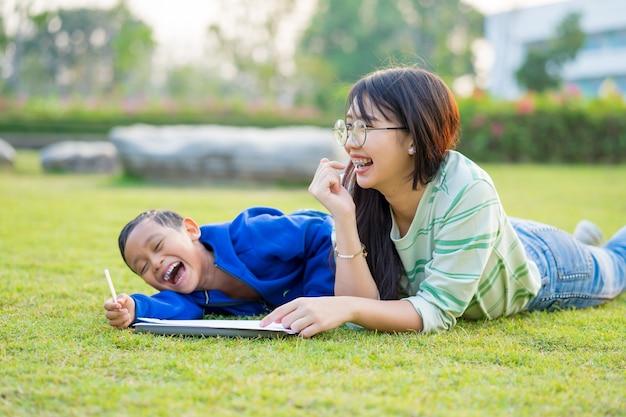 アジアの十代の女の子は緑の牧草地で素敵で楽しい少年を教えます