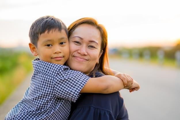 アジアのおばあちゃん、夕日に愛されて息子を抱きしめる