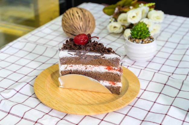 Кусочек торта шварцвальд на деревянной тарелке