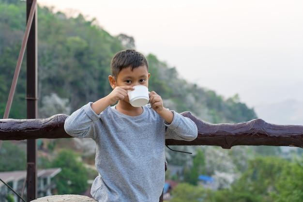 アジアの子供男の子はガラスから水を飲んでいます。山の景色を背景に