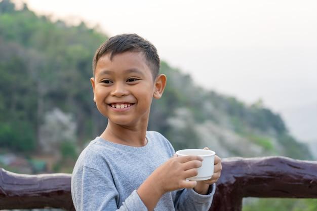 アジアの子供男の子は、ガラスから水を飲んでいます。山の景色を背景に