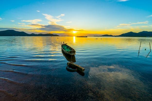 バンプラ貯水池、シラチャチョンブリー、タイで夕日と漁船