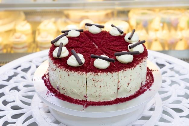 白いテーブルに赤いベルベットのチーズケーキ