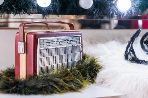メイクアップテーブルの前に白い毛皮のビンテージラジオ受信機。