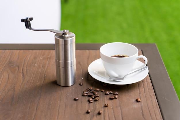 テーブルの上のコーヒーグラインダーとコーヒーカップ