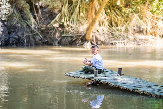 子供の少年は湖の横にある竹橋の上に座る