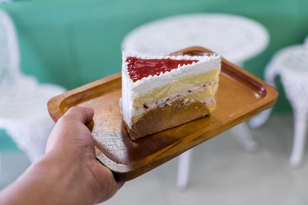 手に木の皿にイチゴのケーキ