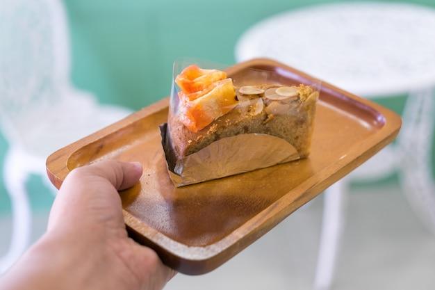 手に木の皿にバエルのフルーツケーキ