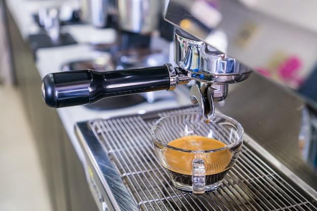 コーヒーマシンから蒸留されたグラスに入ったコーヒー