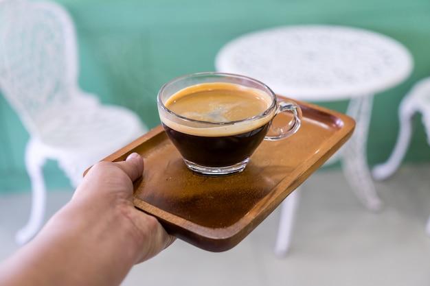 コーヒーショップでウェイトレスの手で木の板にガラスのコーヒー。