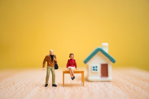 Миниатюрные люди, женщина и мужчина остаются перед домом на оранжевом фоне, используют для бизнеса