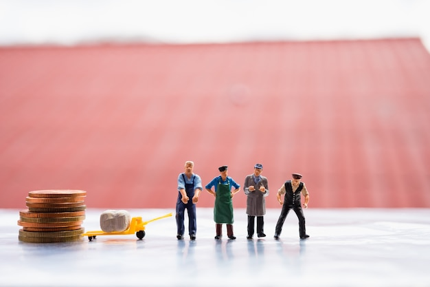 ミニチュアの人々、物流チーム、貨物とコインを職場に持ち、ロジスティックとビジネスの共同利用