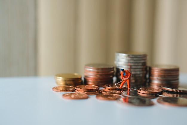 ミニチュアの人々、ビジネスと財務のコンセプトとしてスタックコインを使って作業する男