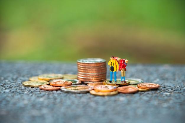 ミニチュアの人々、旅行と財政の概念として使用してスタックコインに立つカップルバックパッカー