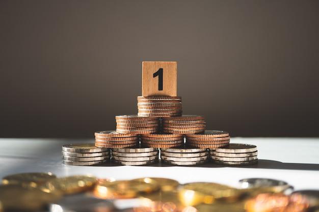 ビジネスと金融の概念として使用するスタックコインのクローズアップナンバーワンの木製ブロック