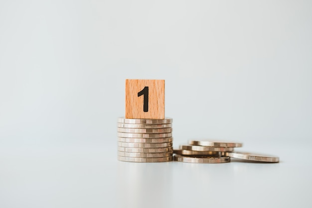 ビジネスと金融の概念として使用するスタックコインのクローズアップの木製ブロックナンバーワン