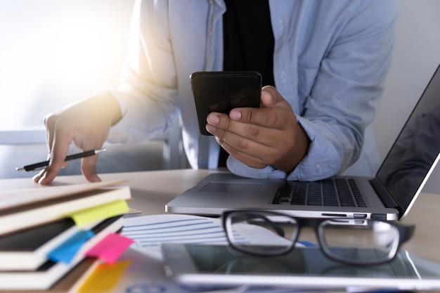 電話スマートフォンとノートパソコンを使用して実業家