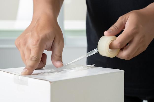 人の手の透明な男包装箱粘着テープ。
