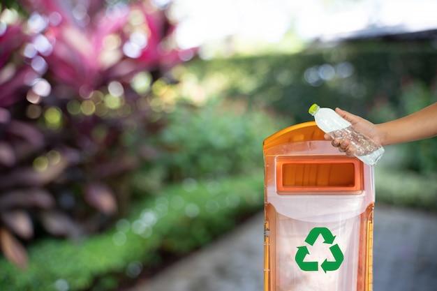 人間の手は、リサイクルコンセプトのためのプラスチックリユースを置く環境保護の世界のリサイクル