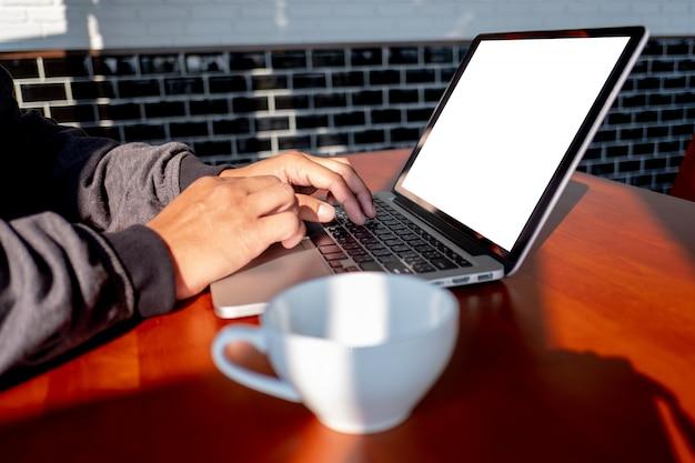 木製の机の上のラップトップコンピューターに取り組んでいるビジネスの男の手の男テーブルの上の空白の画面を持つノートパソコン