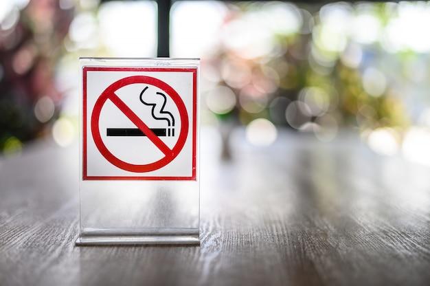 コーヒーショップで木製のテーブルに禁煙の標識