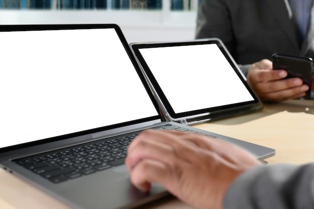 テーブルの上に空白の画面を持つノートパソコン。広告テキストメッセージの空白のコピースペース画面を持つラップトップコンピューター上のワークスペースの新しいプロジェクト