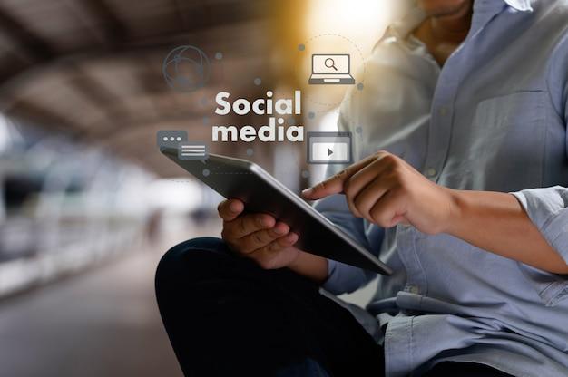 ソーシャルメディアネットワーク図を持つ木製の机の上のラップトップコンピューターに取り組んでいるビジネスの男の手の二重露光
