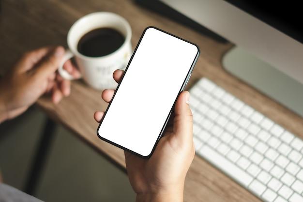 空白の画面で携帯電話を保持しているスマートフォンの男性を使用して平面図モックアップ画像手