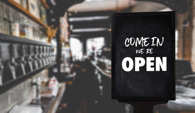 コーヒーショップヴィンテージレトロな看板の前に立っているカフェのウェイターコーヒーでオープンサイン