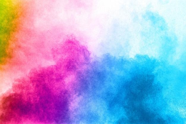 白い背景に抽象的な色の粉の爆発。ほこりのスプラッシュのフリーズの動き