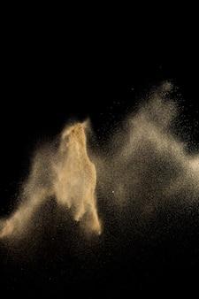 乾いた川の砂の爆発。黄金色の砂のスプラッシュ、黒の背景。