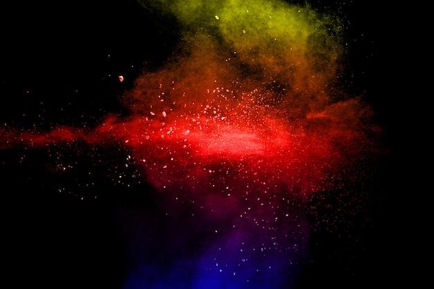 黒い背景に複数の色の粒子の爆発。暗い背景に色とりどりの埃が飛び散る。