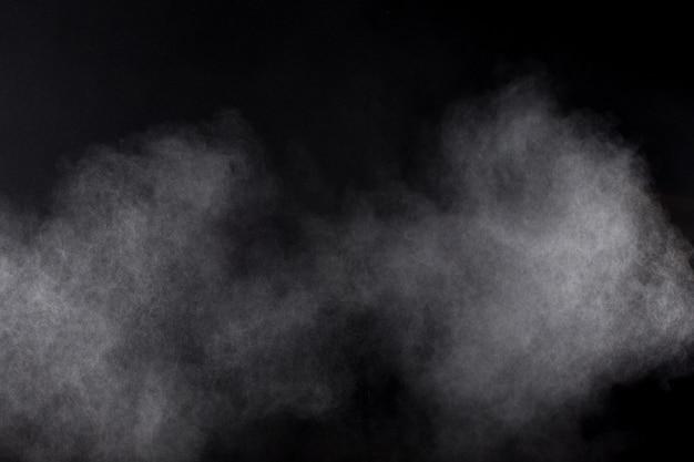 黒い背景に白い粉の爆発雲の奇妙な形。白い塵の粒子が飛び散る。