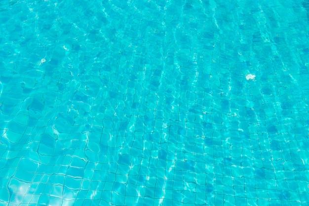 スイミングプールの青緑色の水。スイミングプールのバックグラウンドでのパターンの表面。
