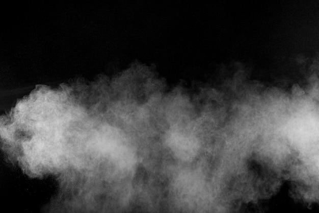 黒い背景に抽象的な白い粉の爆発。抽象的な白い粉塵が吐き出す。