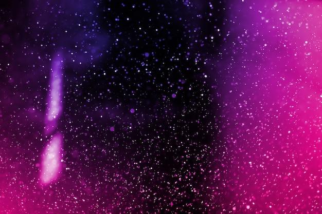 黒の背景に浮かぶ抽象的な本物の紫色の塵。グランジデザインのオーバーレイ用のダスト粒子。ぼやけたダストコンセプト。