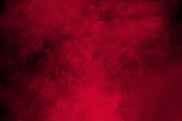 黒の背景に抽象的な赤い煙。劇的な赤い煙雲。