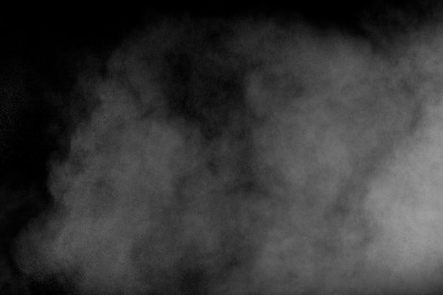 Белая пыль выдыхается в воздухе. порошок движения взрыва в темном фоне.