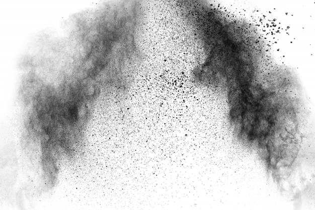 黒い粒子は白い背景の上に飛び散ります。黒い粉塵の破裂