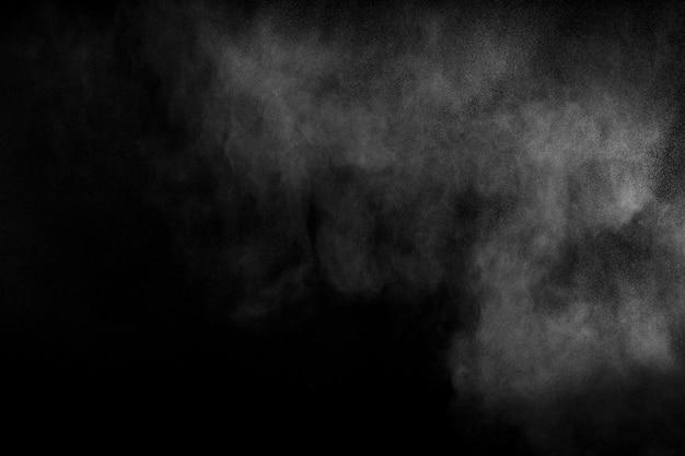 黒い背景に対して抽象的な粉体爆発。白いほこりが空気中に吐き出します。