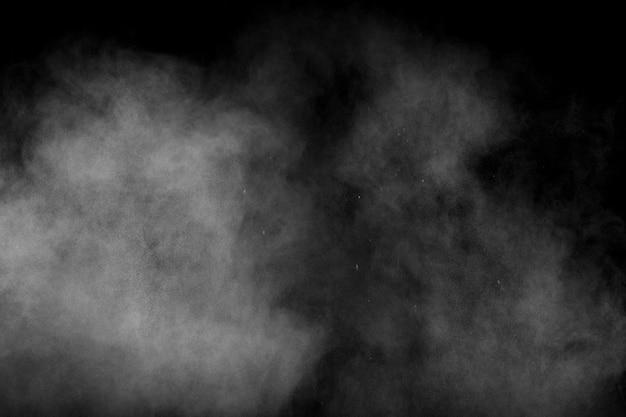 Абстрактный белый порошок взрыв на черном фоне. белая пыль выдыхает в воздухе.
