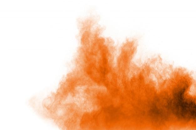 白い背景の上のオレンジ色のほこりの抽象的な爆発。