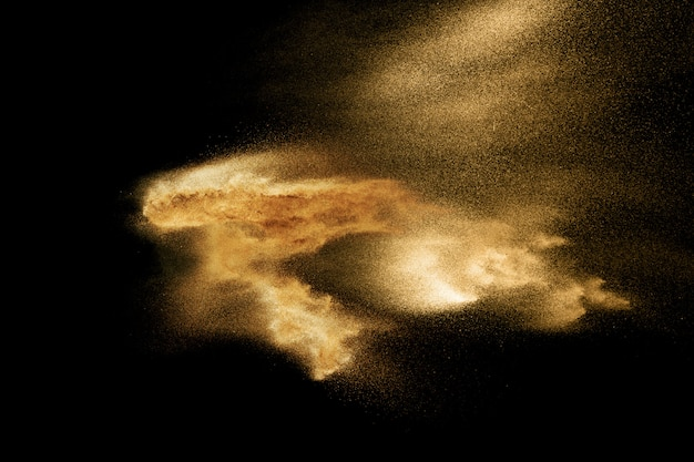 黒の背景に分離された砂の爆発