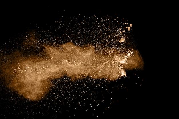 茶色の粒子が黒い背景に飛び散った
