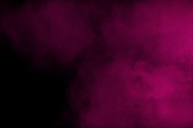 黒の背景に分離されたピンク色の粉の爆発。