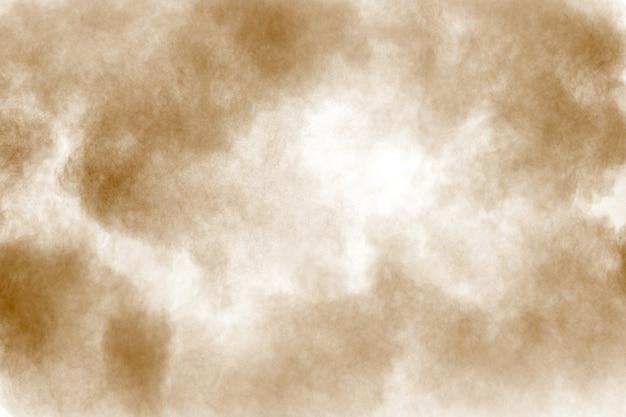 茶色のほこりの雲。茶色の粒子が白い背景に飛び散った。