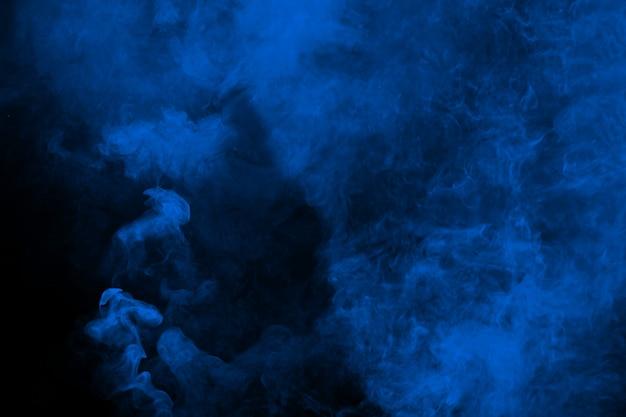 黒の背景に抽象的な青い煙。