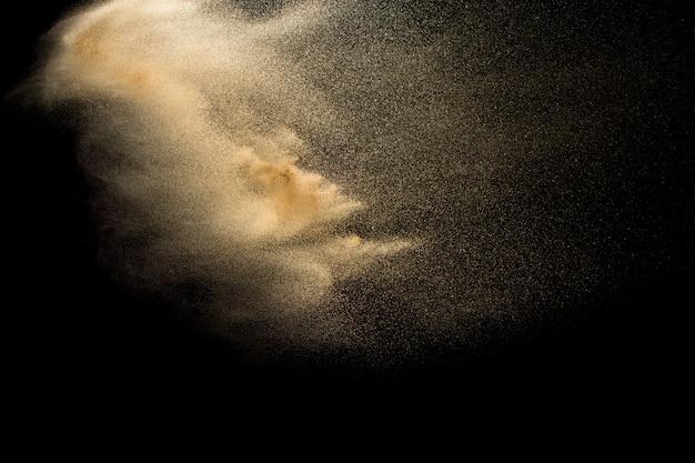 空気中の黄色い砂のハエの波。黒の背景に砂が爆発します。