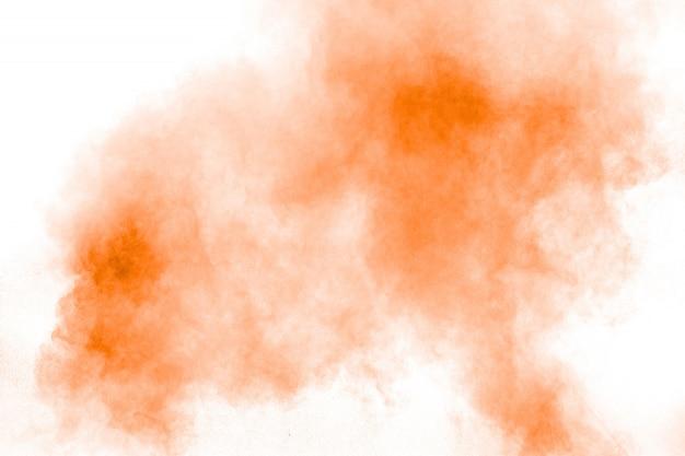 白い背景の上の抽象的なオレンジ粉の爆発。オレンジ色の塵のしぶきの動きを凍結します。